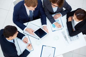 Group of business partners looking at touchscreen while planning work at meeting